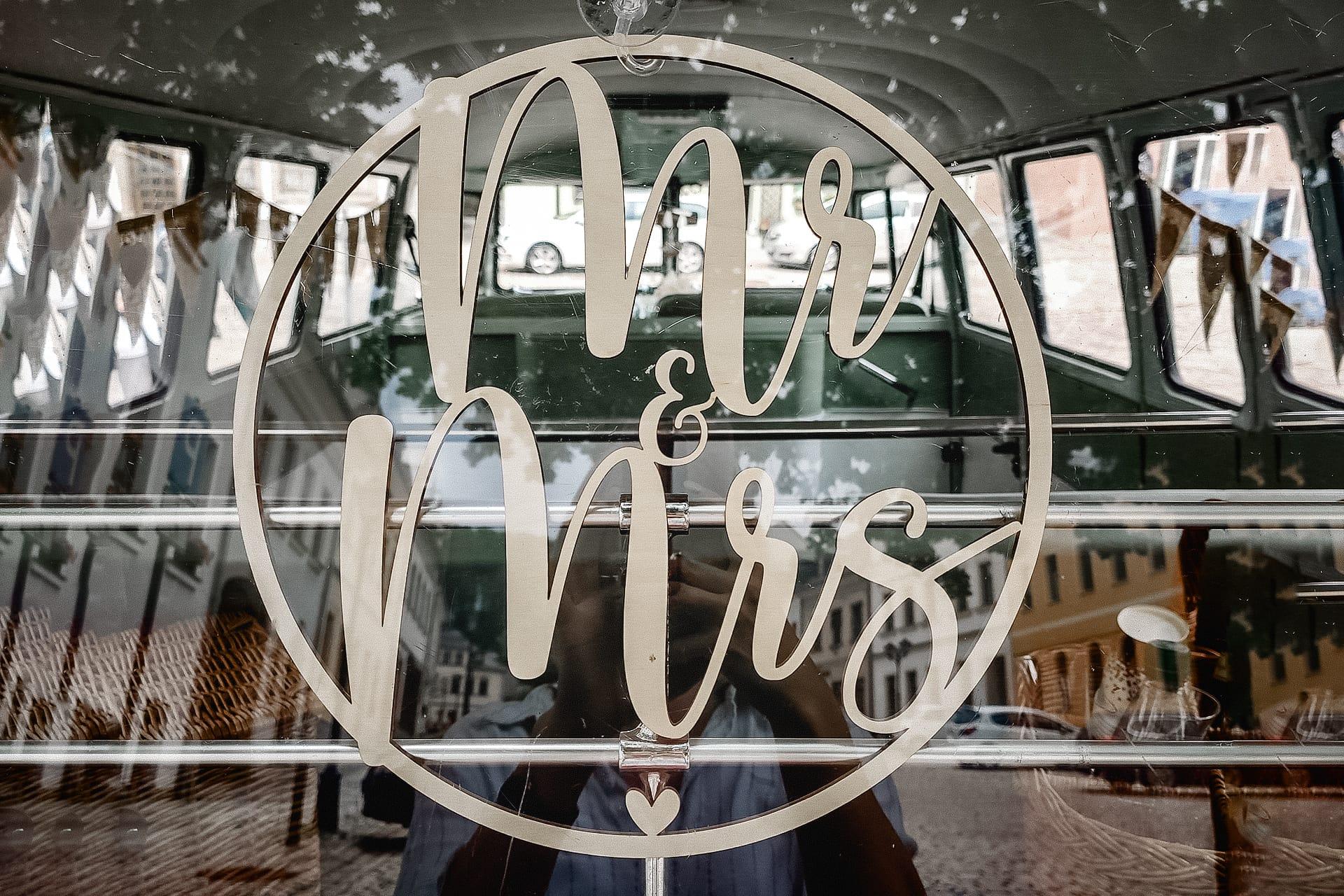Autodekoration aus Holz an einer Heckscheibe eines VW Bulli als Hochzeitsauto mit der Aufschrift Mr. & Mrs.