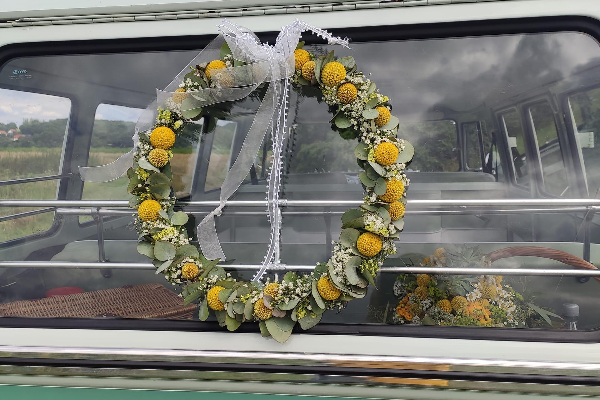 Echtblumen Kranz in gelb und weiß mit Craspedia und Eukalyptus an der Heckscheibe eines Oldtimers VW T1 Bus
