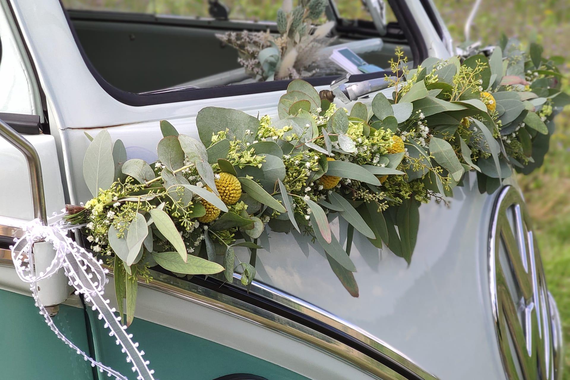 Echtblumengirlande in gelb, weiß mit Eukalyptus und Craspedia an einem Hochzeitsauto VW T1