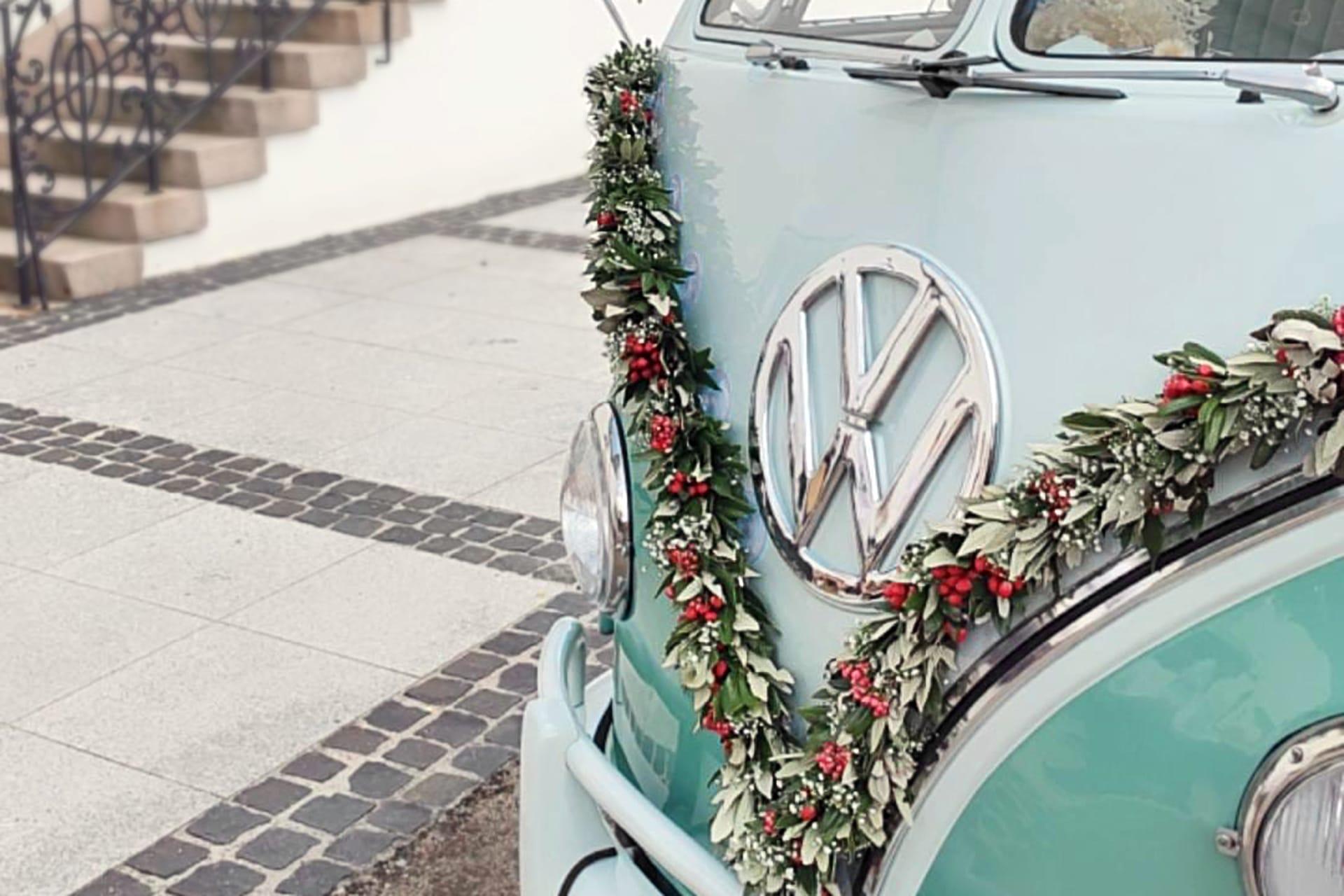 Echtblumengirlande in rot, weiß und Eukalyptus an einem Hochzeitsauto VW Bulli